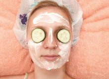 Young woman with cucumber slices on the face in a spa saloon Royalty Free Stock Image