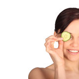 Young woman with cucumber slices on the face in a spa Stock Images