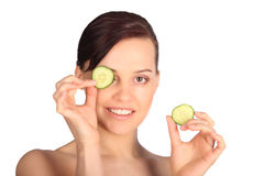 Young woman with cucumber slices on the face in a spa Stock Photos