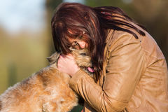 Young woman cuddling with a cute dog royalty free stock images