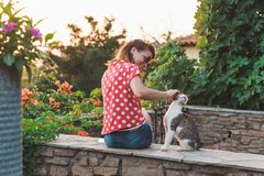 Young woman cuddling a stray cat. In the garden Royalty Free Stock Photography