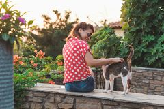 Young woman cuddling a stray cat. In the garden Stock Photography