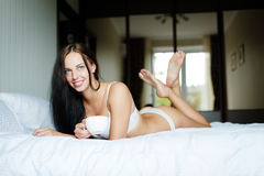 Young woman with a cup in a bed Stock Photo