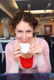 Young woman with cup in cafe Royalty Free Stock Images