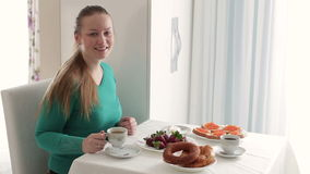 Young woman with a cup of coffee. Breakfast at the girl. Women drinking coffee at breakfast. stock footage