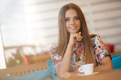 A young woman with a Cup of coffee in a cafe. Portrait of beautiful young woman with gray eyes and long straight brown hair,nice smile,light makeup,wearing Royalty Free Stock Images