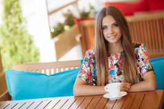 A young woman with a Cup of coffee in a cafe Royalty Free Stock Images