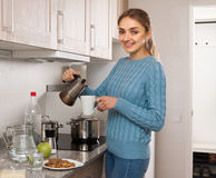 Young woman with a cup of coffee in the kitchen Royalty Free Stock Image