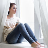 Young woman with cup of coffee looking out of the window Stock Images