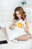 Young woman with Cup of coffee and mobile phone in bed in the morning Stock Photo