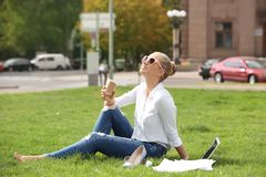 Young woman with cup of coffee sitting on green lawn in park. royalty free stock photography
