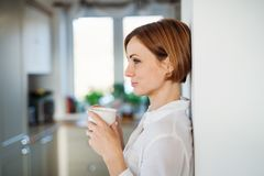A young woman with cup of coffee standing indoors, leaning on a wall. stock images
