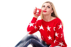 Young woman with Cup of coffee or tea.Cup with a Christmas theme. Cute girl in the red sweater sitting with a Cup of tea or coffee .Cup with a Christmas theme royalty free stock photo