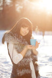 Young woman with a cup of hot drink Winter woman on background o Stock Photos