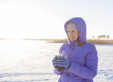 Young woman with a cup of hot drink in winter wood Winter woman on background of winter landscape sun. Royalty Free Stock Photos