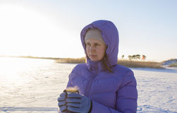 Young woman with a cup of hot drink in winter wood Winter woman on background of winter landscape sun. Royalty Free Stock Image