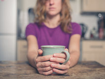 Young woman with cup in kitchen Royalty Free Stock Photos