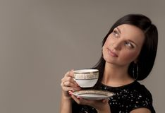 Young woman with a cup of tea. Thoughtful young woman with a cup of tea. Studio picture Stock Photo