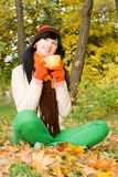 Young woman with cup of tea in the autumn park Stock Images