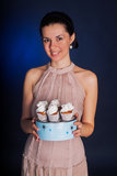 Young woman with cupcakes. Young female cook holding cupcakes stock photography