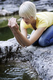 Young woman cupping water from a rock pool Royalty Free Stock Images