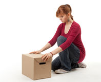 Young woman with curiosity looking on box Royalty Free Stock Photos