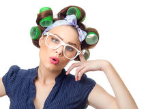 Young woman with curlers. Confused woman with curlers. Funny girl isolated on white background, studio-shot royalty free stock photo