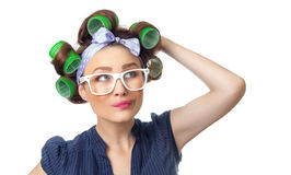 Young woman with curlers. Confused woman with curlers. Funny girl isolated on white background, studio-shot stock image