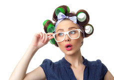 Young woman with curlers. Confused woman with curlers. Funny girl isolated on white background, studio-shot Stock Images