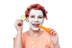 Young woman in curlers and with a mask on her face eating carrot Stock Photo