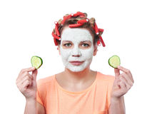 Young woman in curlers and with a mask on her face Royalty Free Stock Image