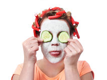 Young woman in curlers and with a mask on her face Royalty Free Stock Images