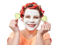 Young woman in curlers and with a mask on her face Stock Photography