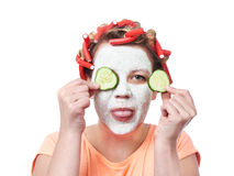 Young woman in curlers and with a mask on her face Stock Images