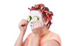 Young woman in curlers and with a mask on her face Royalty Free Stock Photography