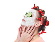 Young woman in curlers and with a mask on her face Royalty Free Stock Photo