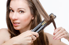 Young woman curling hair with hair straightener Stock Photography