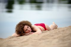 Young woman with curling hair lies on a beach Stock Photos