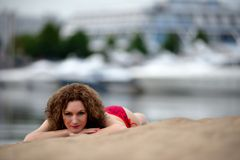 Young woman with curling hair lies on a beach Stock Image