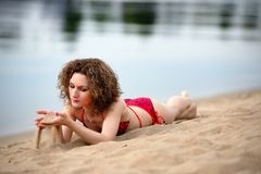 Young woman with curling hair lies on a beach and plays with sand Royalty Free Stock Photography