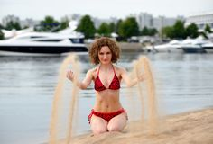 Young woman with curling hair sit on a beach and plays with sand Stock Image