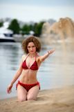 Young woman with curling hair sit on a beach and plays with sand Stock Photography