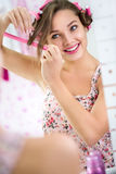 Young woman curling her hair in front  mirror Royalty Free Stock Photography
