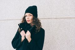 Young woman with curly hair in a black coat. Outdoors Royalty Free Stock Images