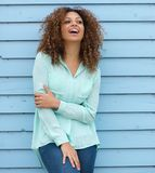 Young woman with curly hair standing outdoors and laughing Royalty Free Stock Images
