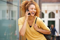 Young woman with curly hair talking on mobile phone in the city royalty free stock photography
