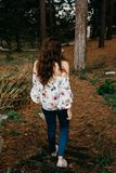 Young woman with curly hair walking through the woods stock photo