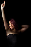 Young woman curly red hair celebrating. Black background Royalty Free Stock Images