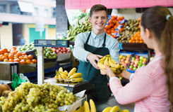 Young woman customer buying yellow bananas Stock Photography