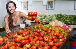 Young woman customer holding fresh ripe tomatoes Royalty Free Stock Photography